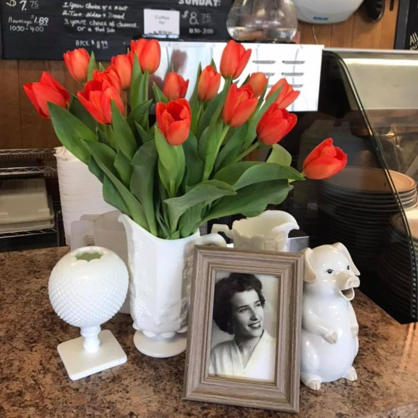 table with flowers and a photo of annie pearl