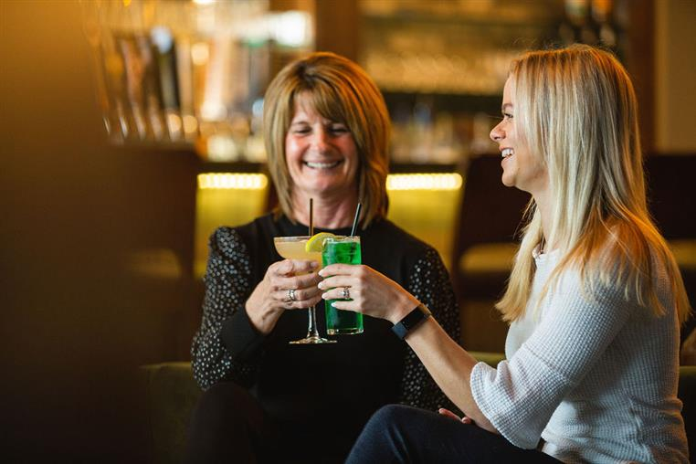 two guest with alcoholic drinks toasting
