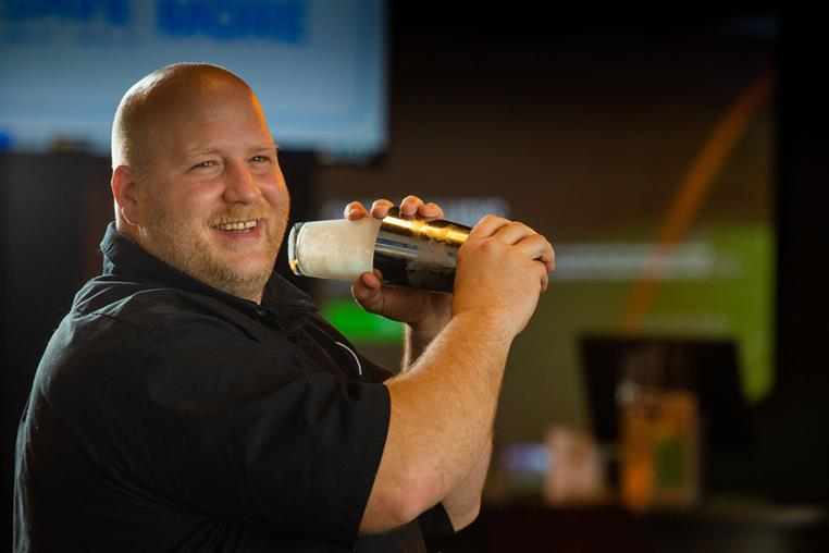 bar tender with shaker shaking a mixed drink