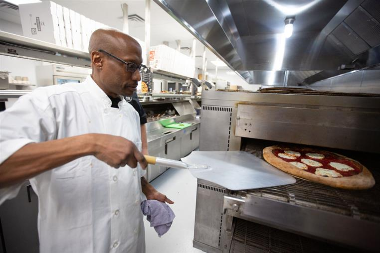 chef removing margherita pizza from oven