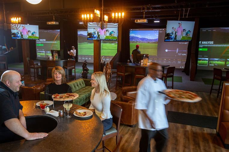 busy bar counter with guests, chef waiting with pizza, and simulator suites