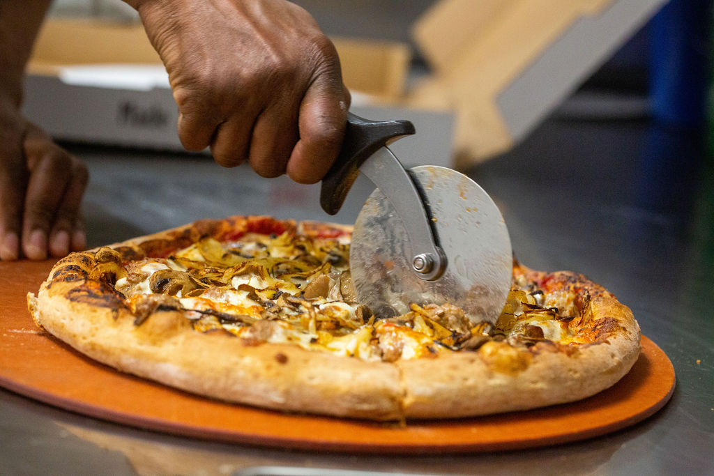 hand slicing pizza pie with pizza cutter
