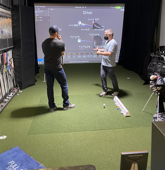 Standard golf lesson with guest and instructor at simulator suite