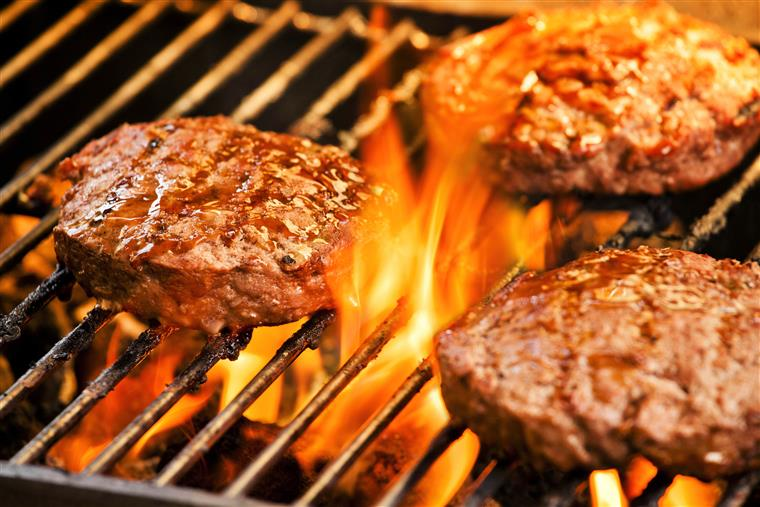 Burger patties on a flame grill