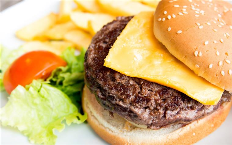Cheese burger on a plate with lettuce, tomato and French fries