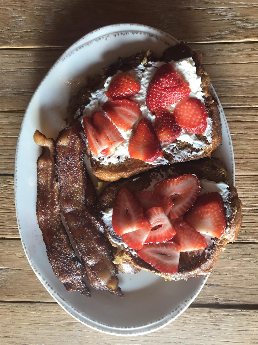 french toast with whipped cream and strawberries on top and bacon on the side