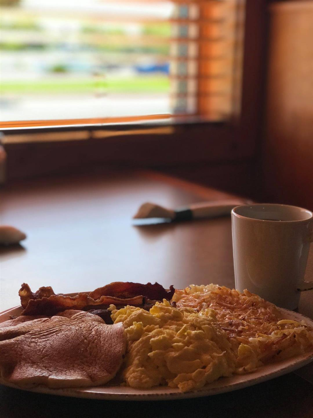 pancake, eggs, and bacon on a plate with a cup of coffee