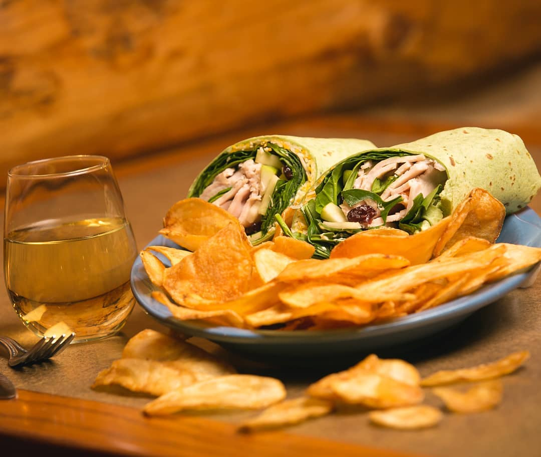 ham wrap with chips and a glass of wine
