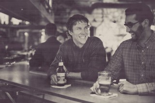 2 men sitting at the bar smiling with drinks in their hands