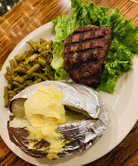 steak filet with a baked potato and green beans