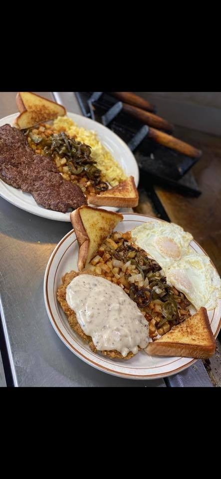 two plates with eggs, hashbrowns, toast, and chicken fried steak