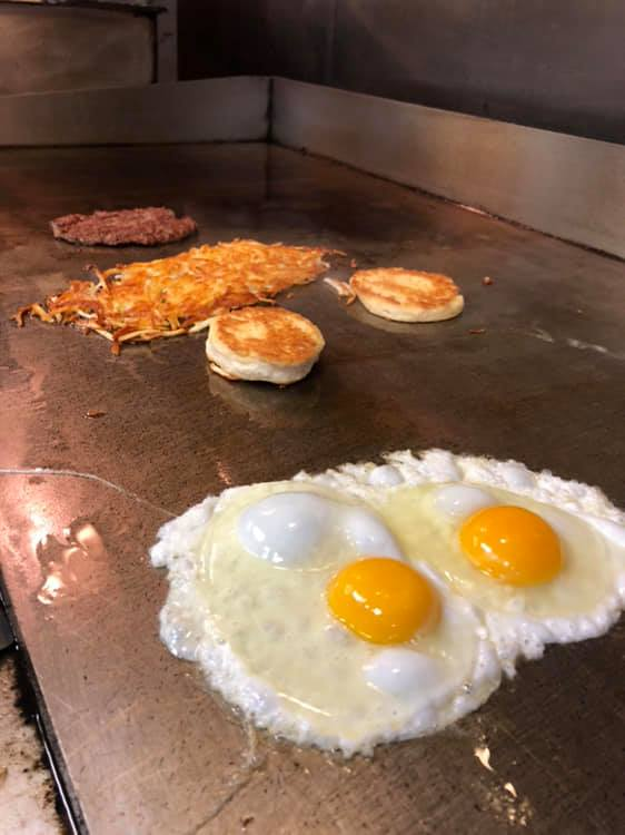 two fried eggs with hashbrowns and biscuits on a grill