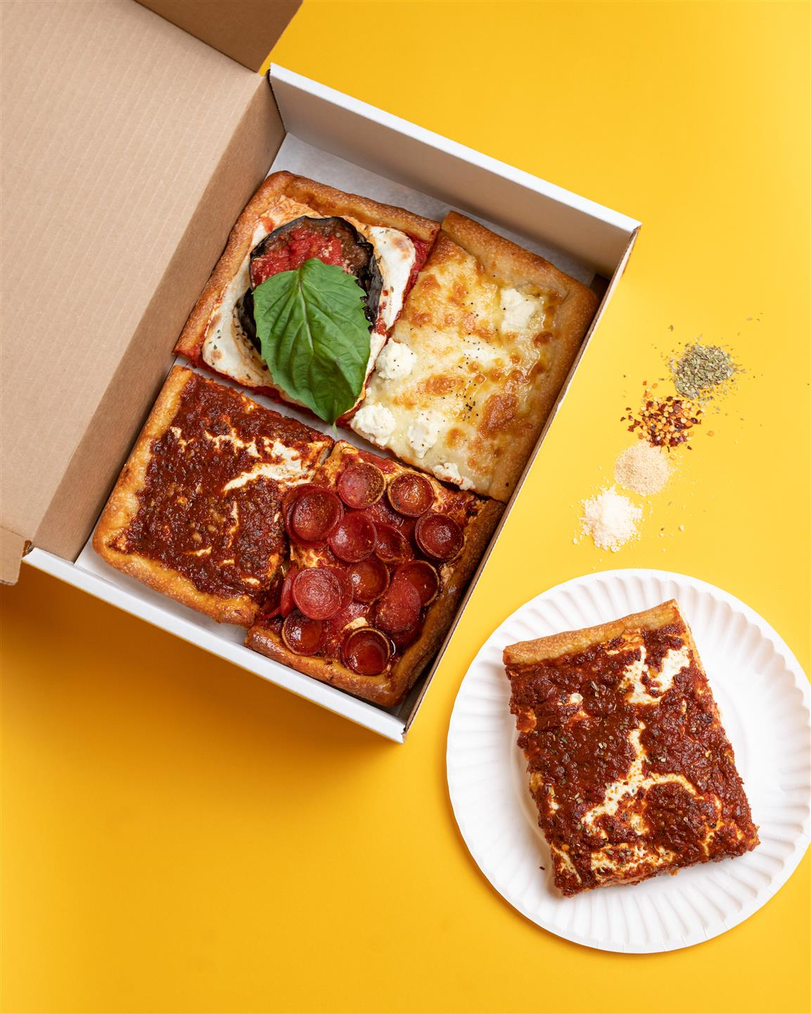 assorted square pizza slices in a box