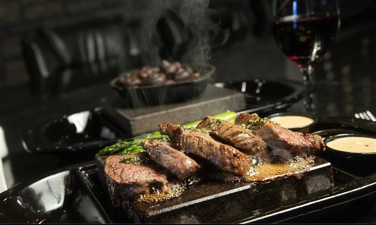 steaks on stone with red wine glass