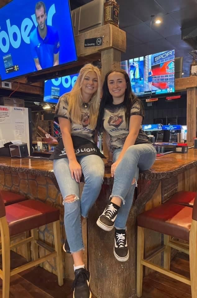 2 employees sitting on the bar for a photo