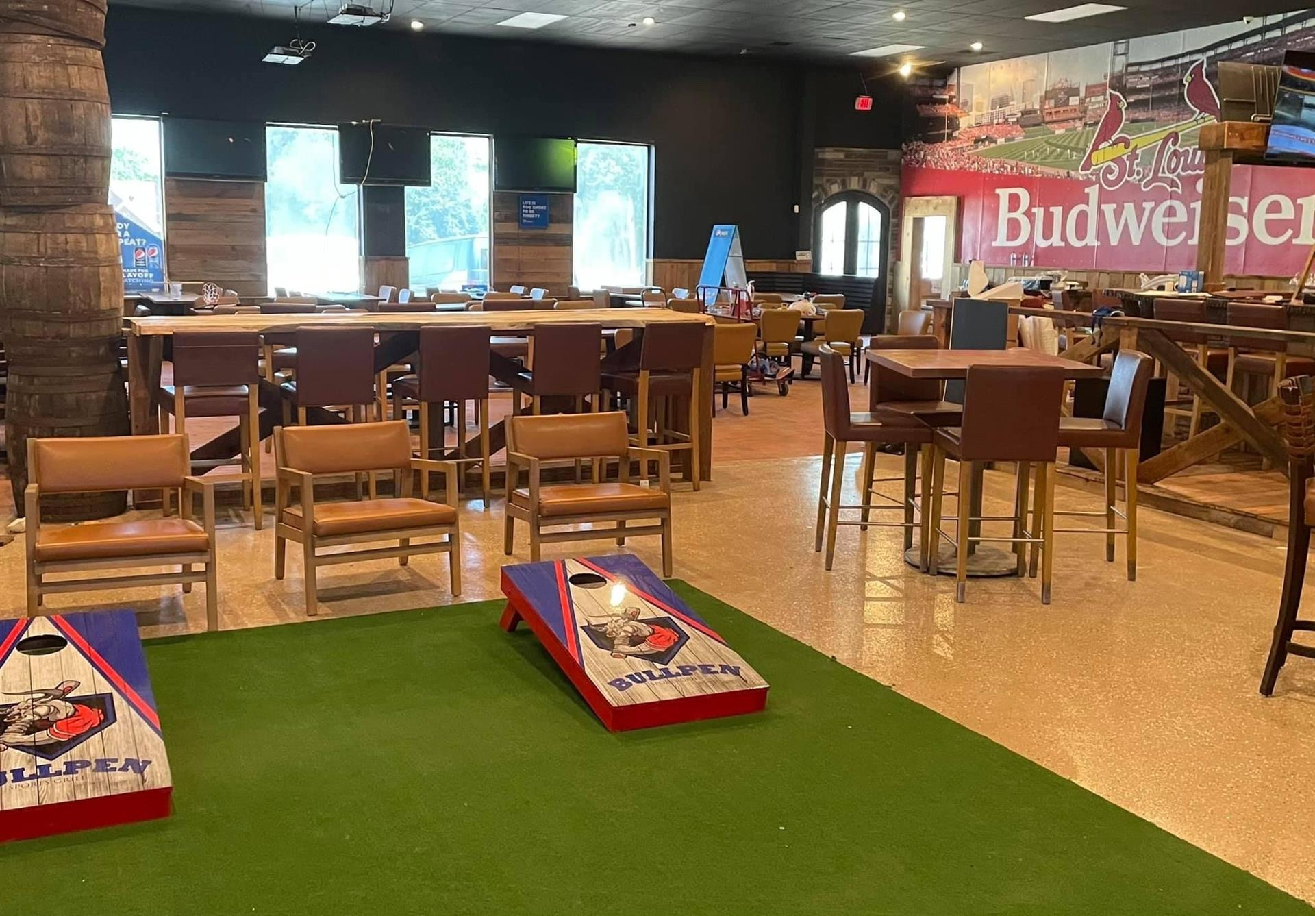 inside of the bullpen sports grill with corn hole and bar tables