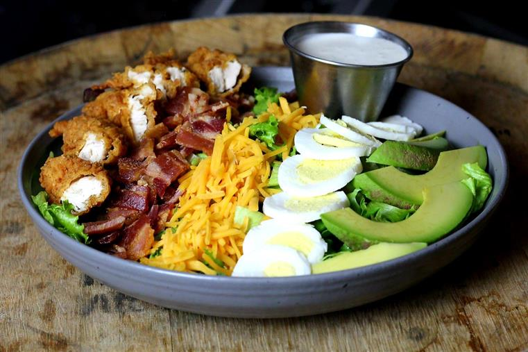 THE COBB salad: Grilled or crispy chicken, chopped bacon, boiled egg, cheddar, diced avocado, mixed greens, tossed in ranch