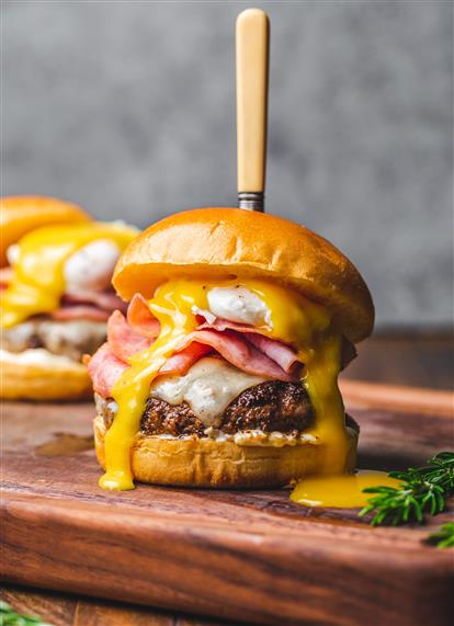 cheeseburger topped with sliced ham and a poached egg with a knife running through it on a cutting board