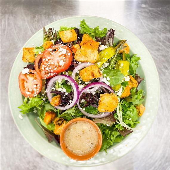 salad with tomatoes, onions, lettuce, and croutons on a plate