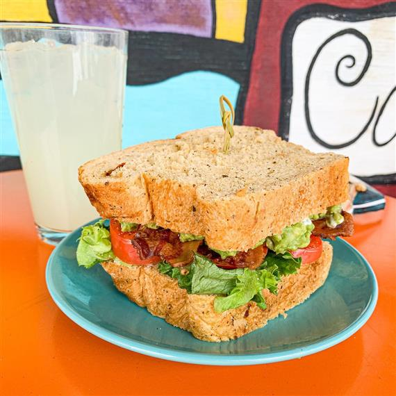 blt sandwich on a plate with a glass of lemonade