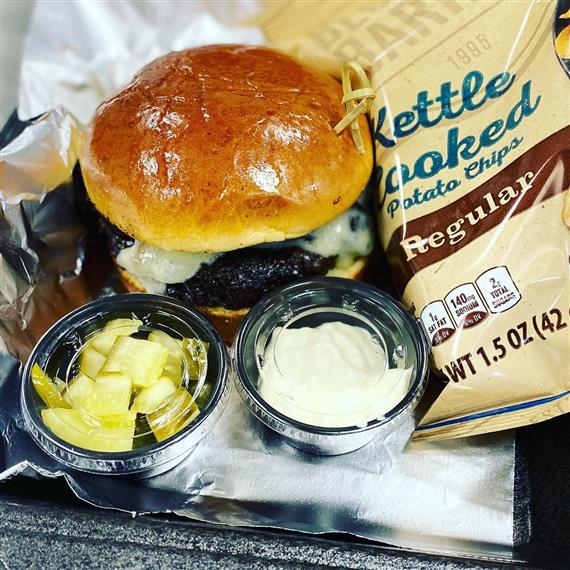hamburger with kettle cooked potato chips and side condiments