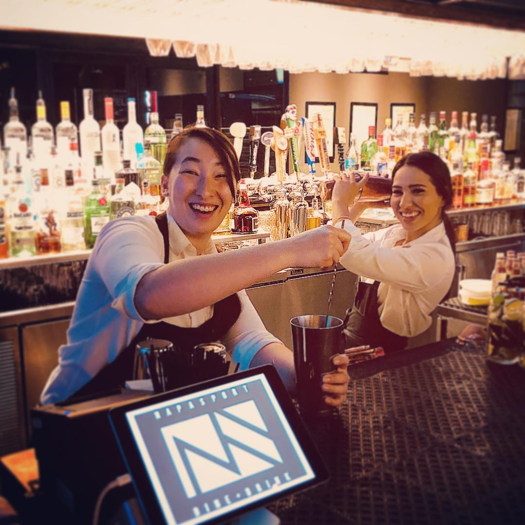 two bartenders posing for a photo behind the bar