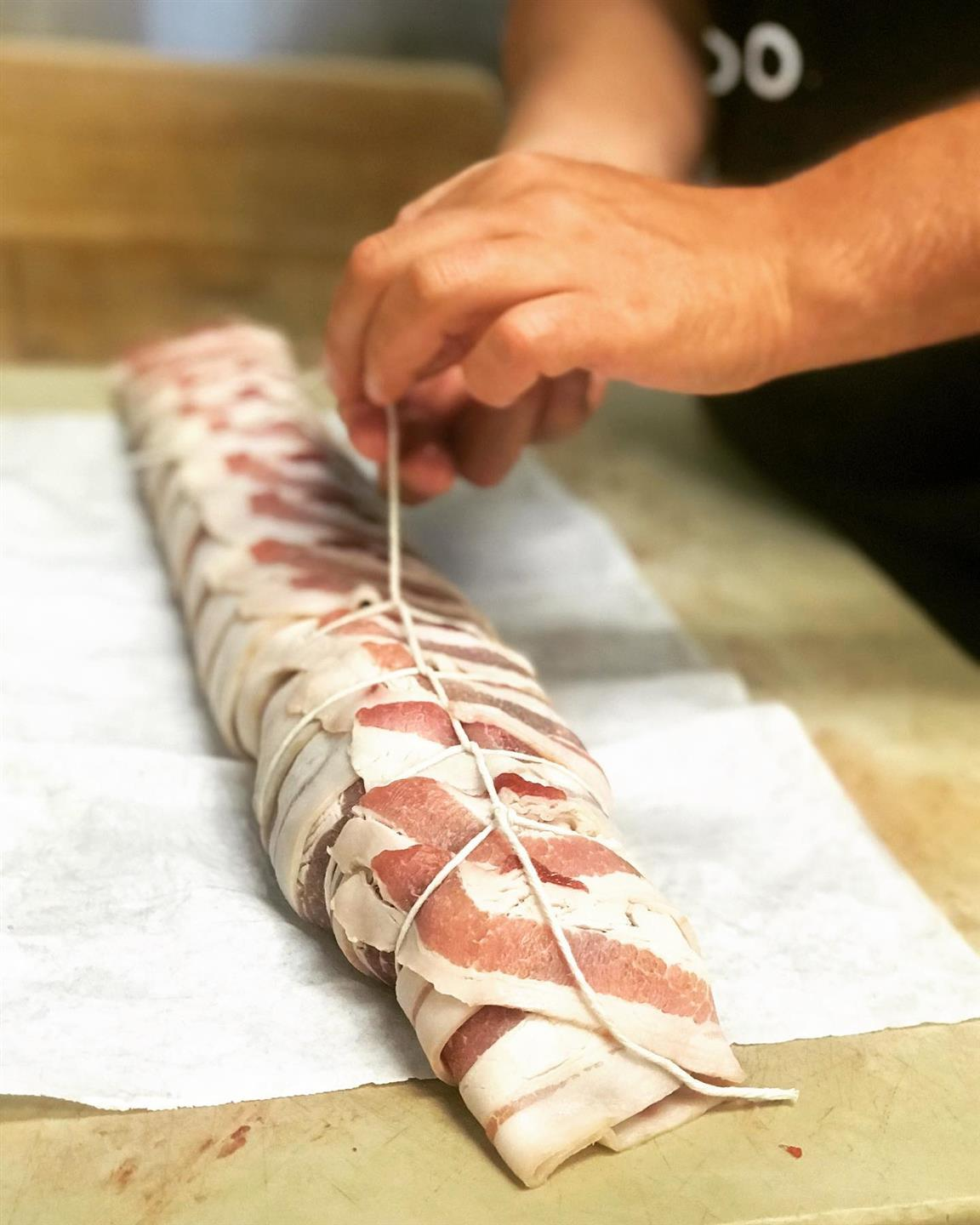 chef rolling bacon around meat