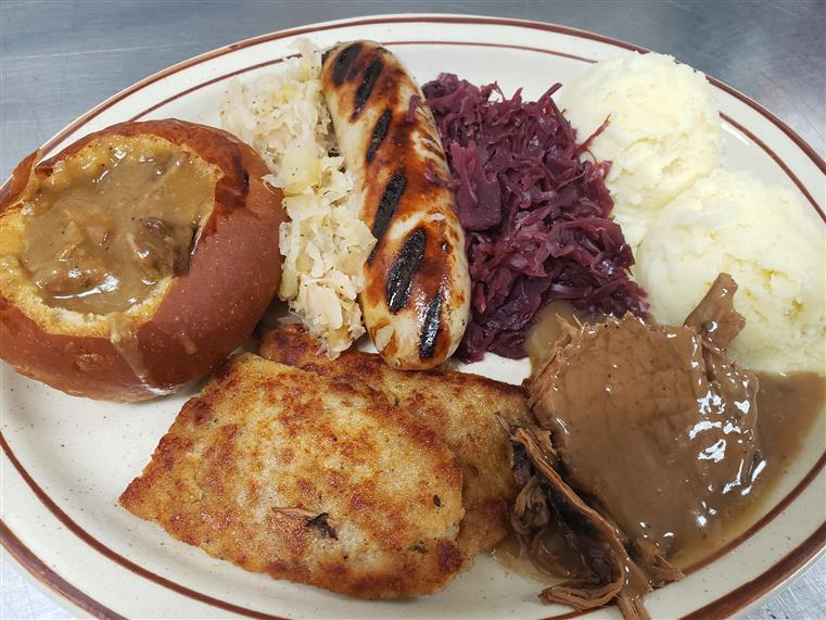 grilled chicken sausage with pulled pork, schnitzel, cabbage and gravy in a mini bread bowl