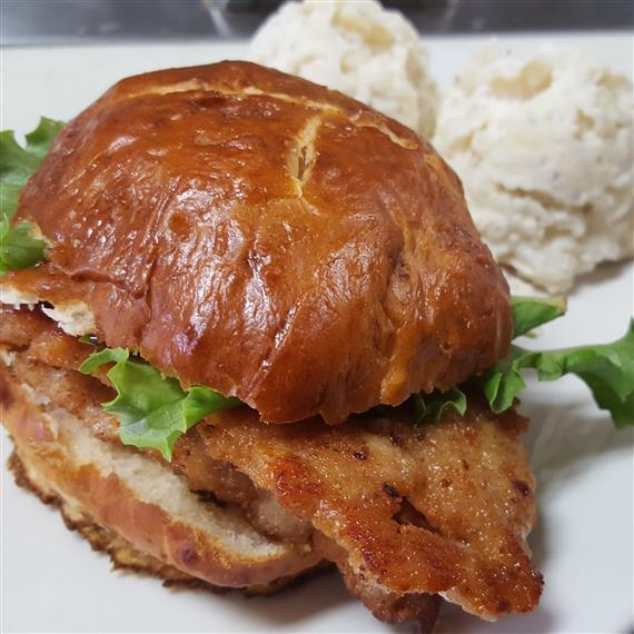 schnitzel sandwich with mashed potatoes on the side