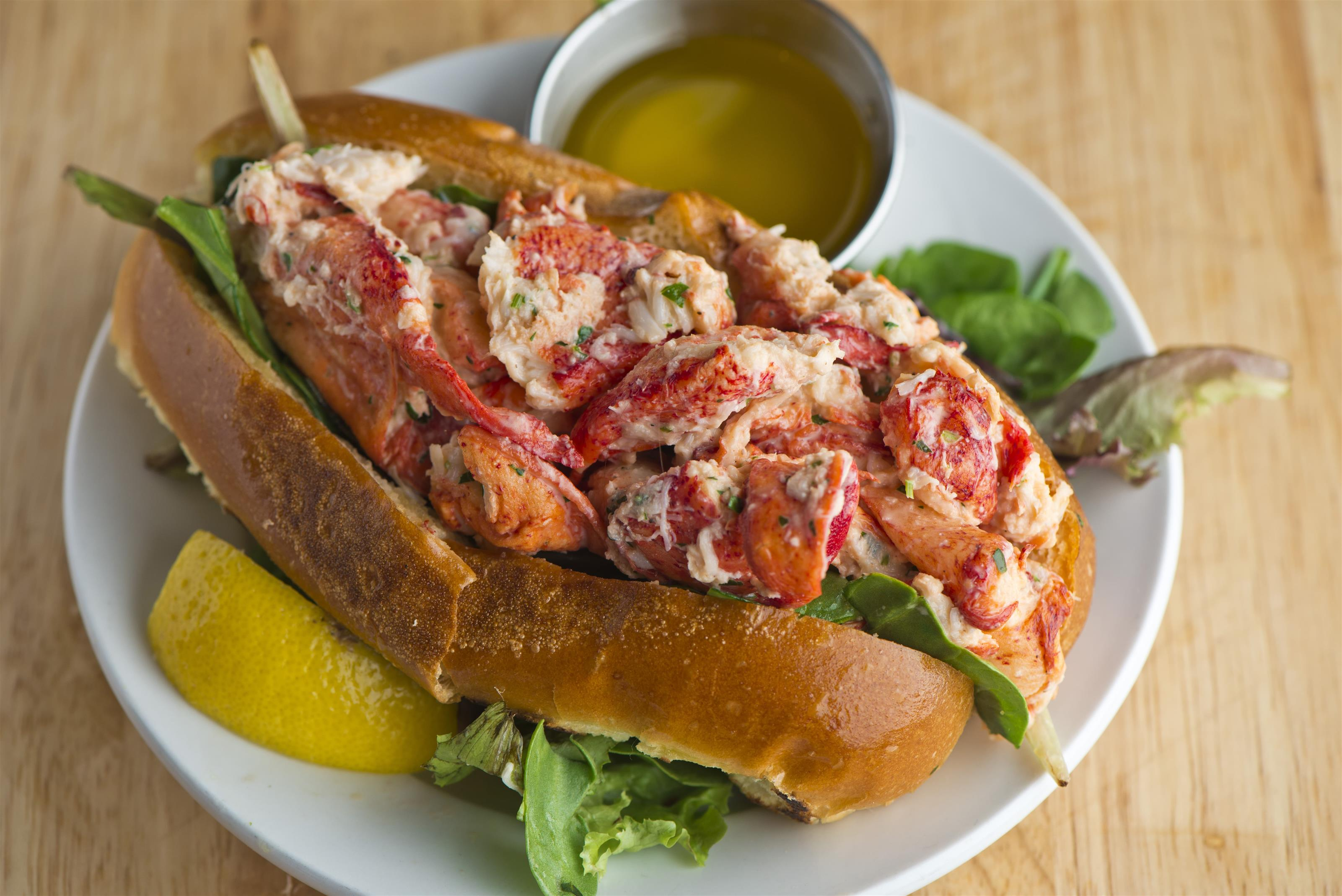 Lobster roll on a bed of lettuce with butter sauce and a lemon wedge