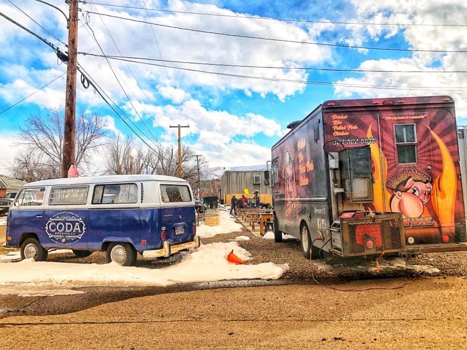 food truck and vw bus parked in an outdoor dining area