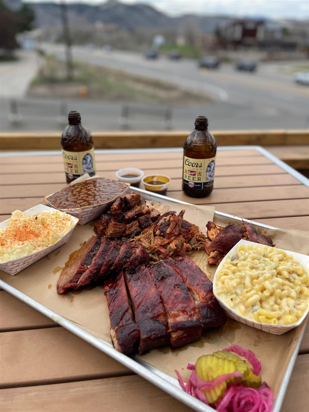 tray of food with two bottles on a picnic table