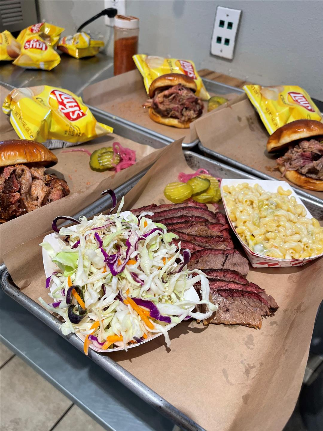 trays with ribs and pulled pork sandwiches with lays potato chips