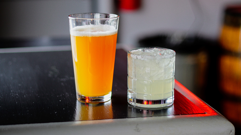 a beer and cocktail on a bar top