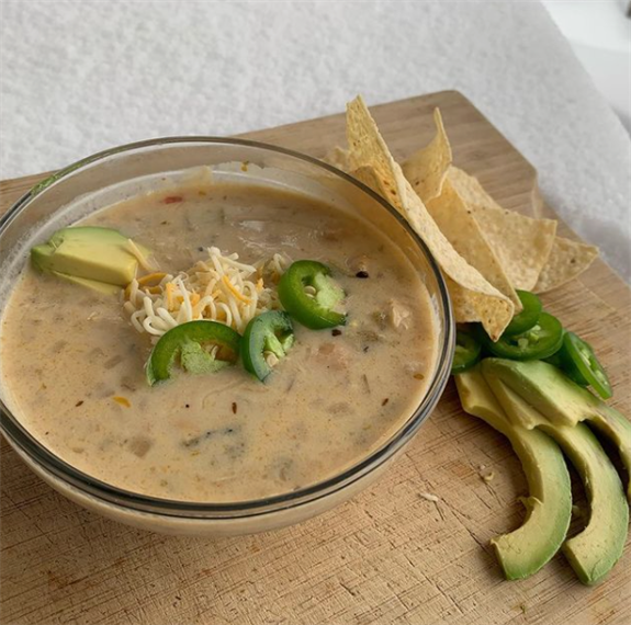White Chicken Chili topped with jalapenos, avocados, and cheese