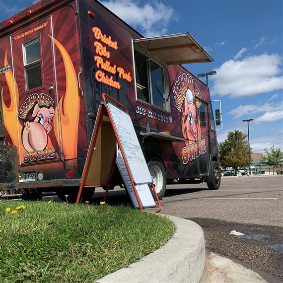 food truck parked in lot with menu sign