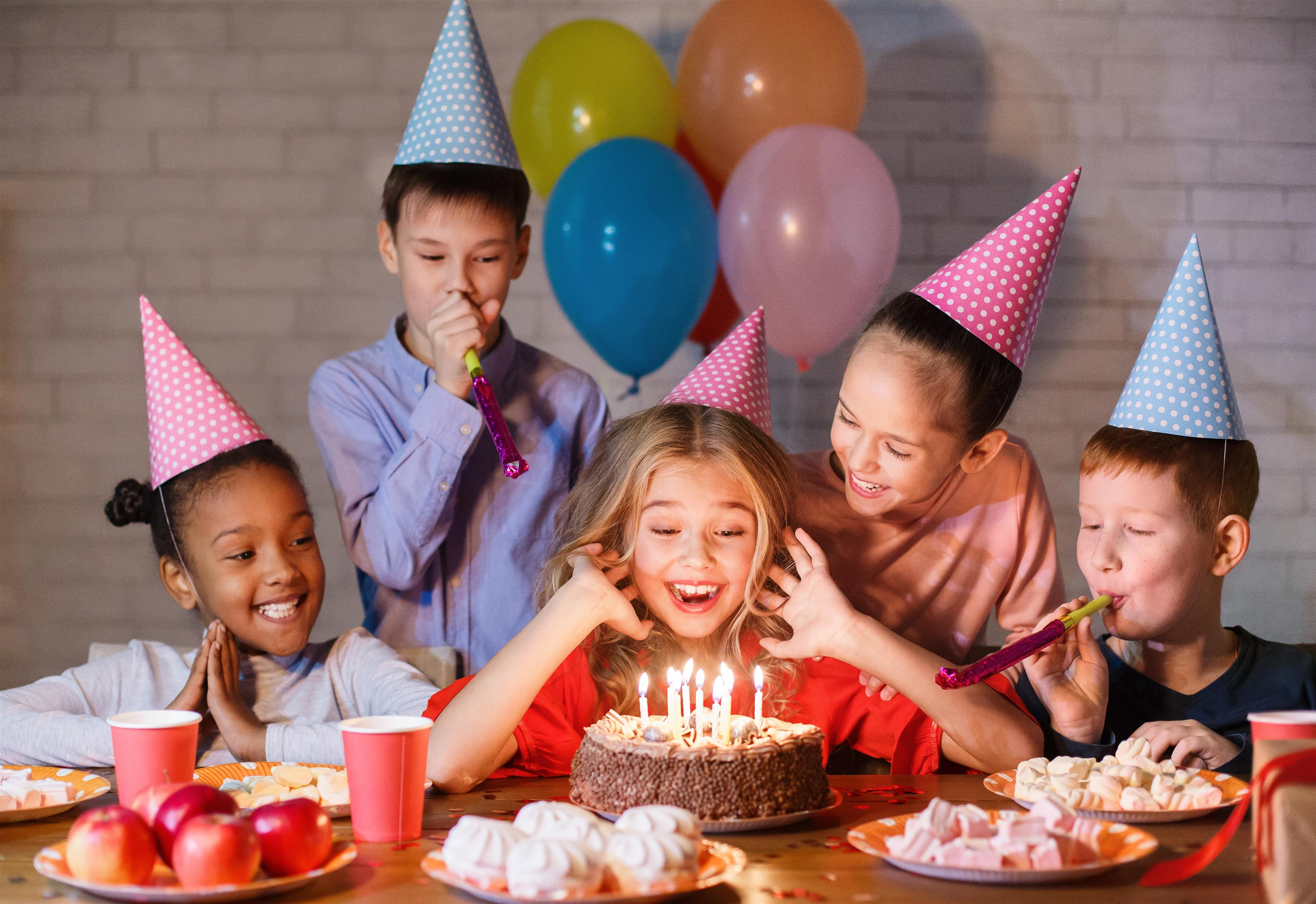 kids with with birthday cake and birthday hats