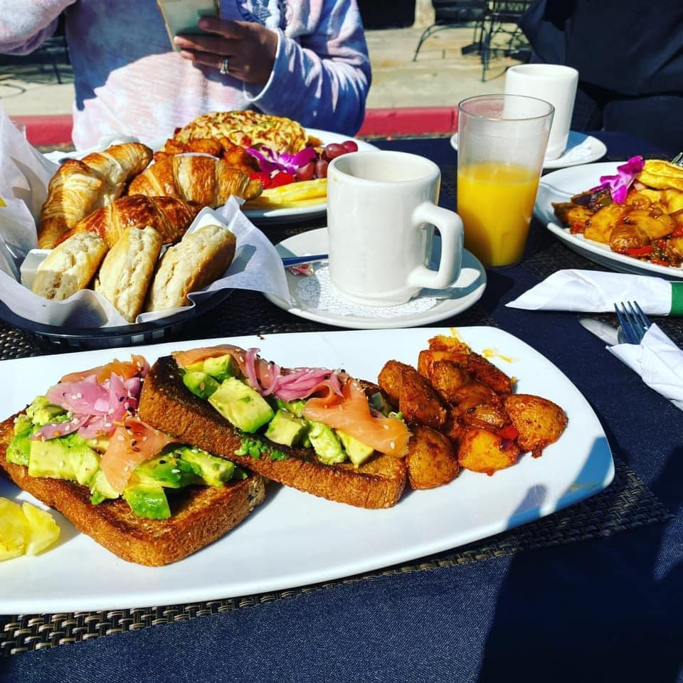 avocado toast with glass of ornage juice, croissant, and other breakfast items