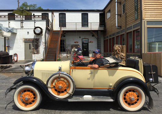 a man sitting in an old car in front of mark twain brewing company