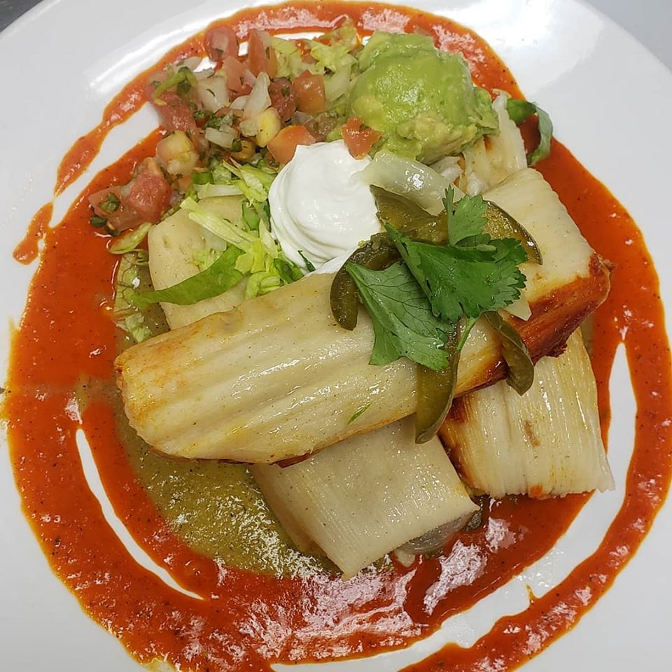 plate of tamales with salsa and cream
