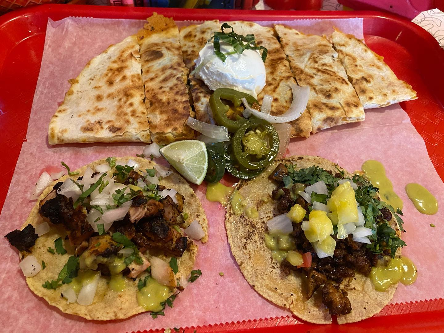 two beef tacos on a plate and a quesadilla