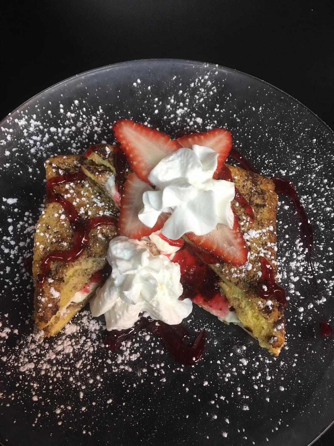 french toast with strawberries, strawberry drizzle, powdered sugar and whipped cream on top