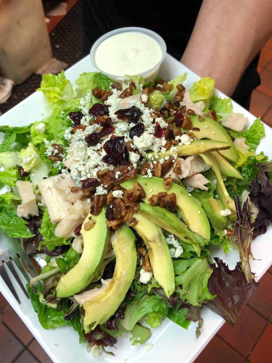 salad with avocado, chicken, cheese, pecans, and raisins on top