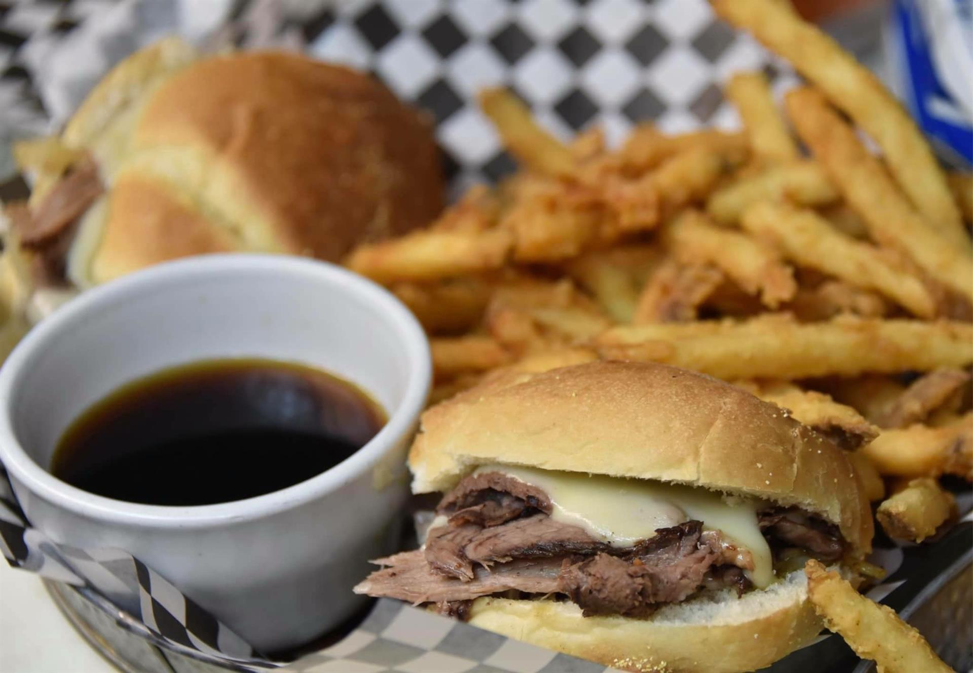 brisket with cheese sandwich, fries and a dipping sauce on the side