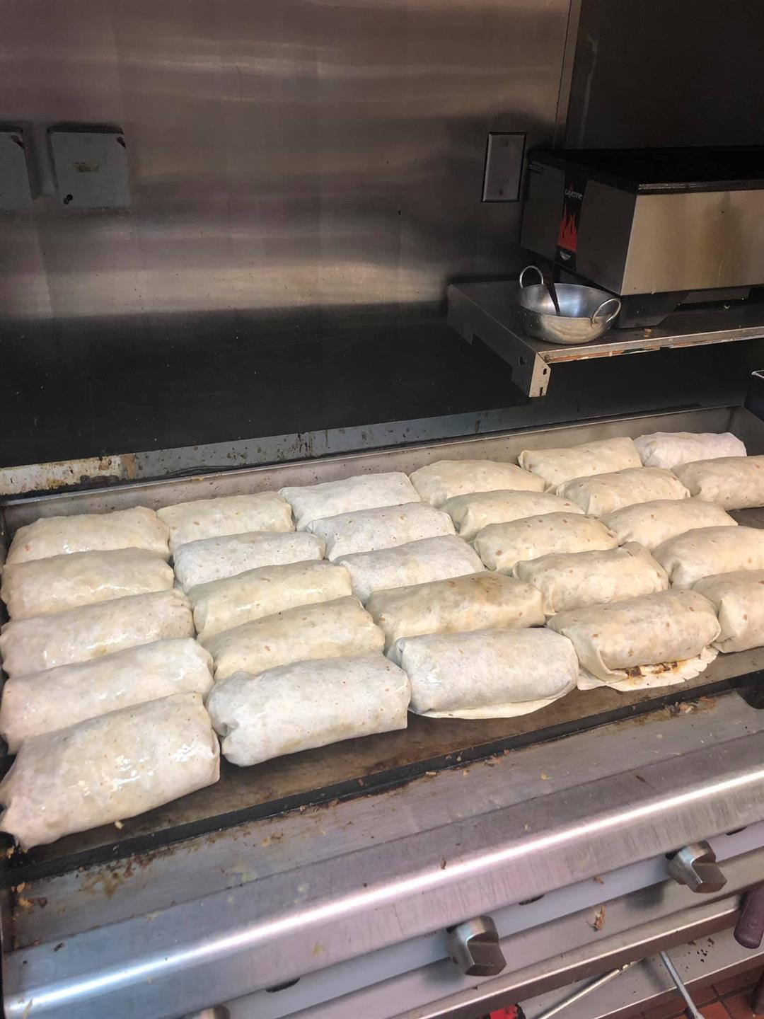 multiple burritos lined up in the kitchen