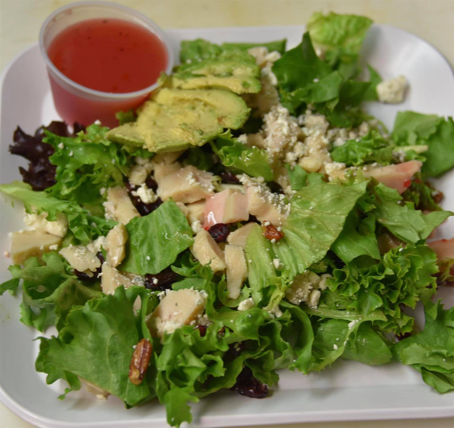 salad with chicken, avocado, and pecans with a raspberry vinagrette dressing on the side