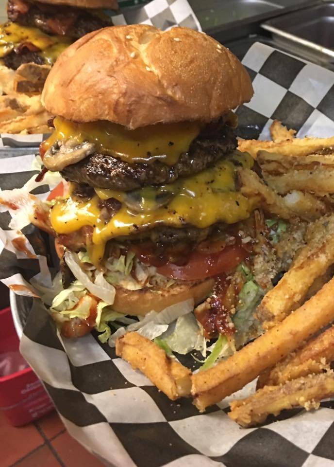 double cheeseburger with lettuce, tomatoes, and mushrooms with fries on the side