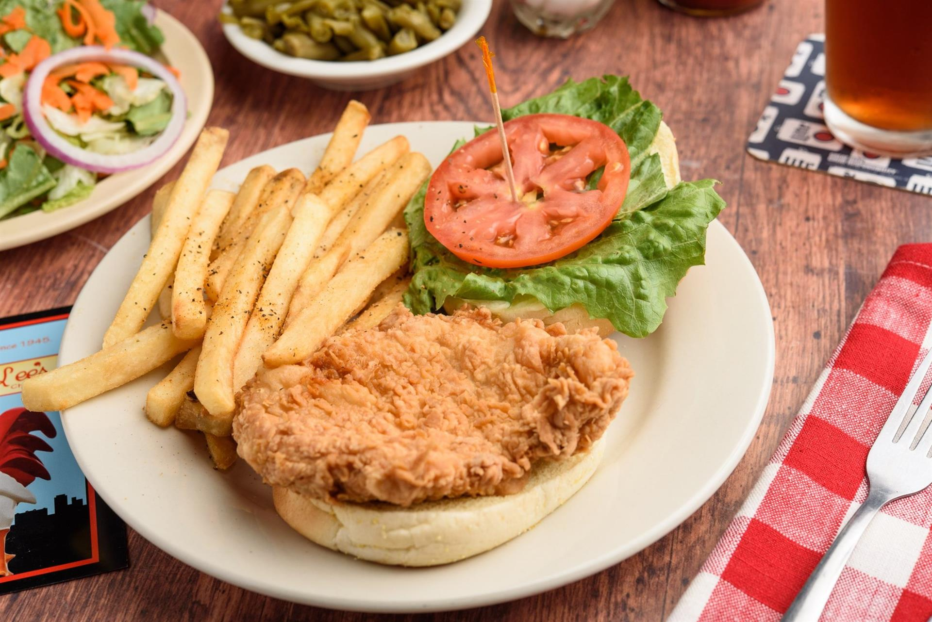 fried chicken sandwich with lettuce, tomato and a side of fries