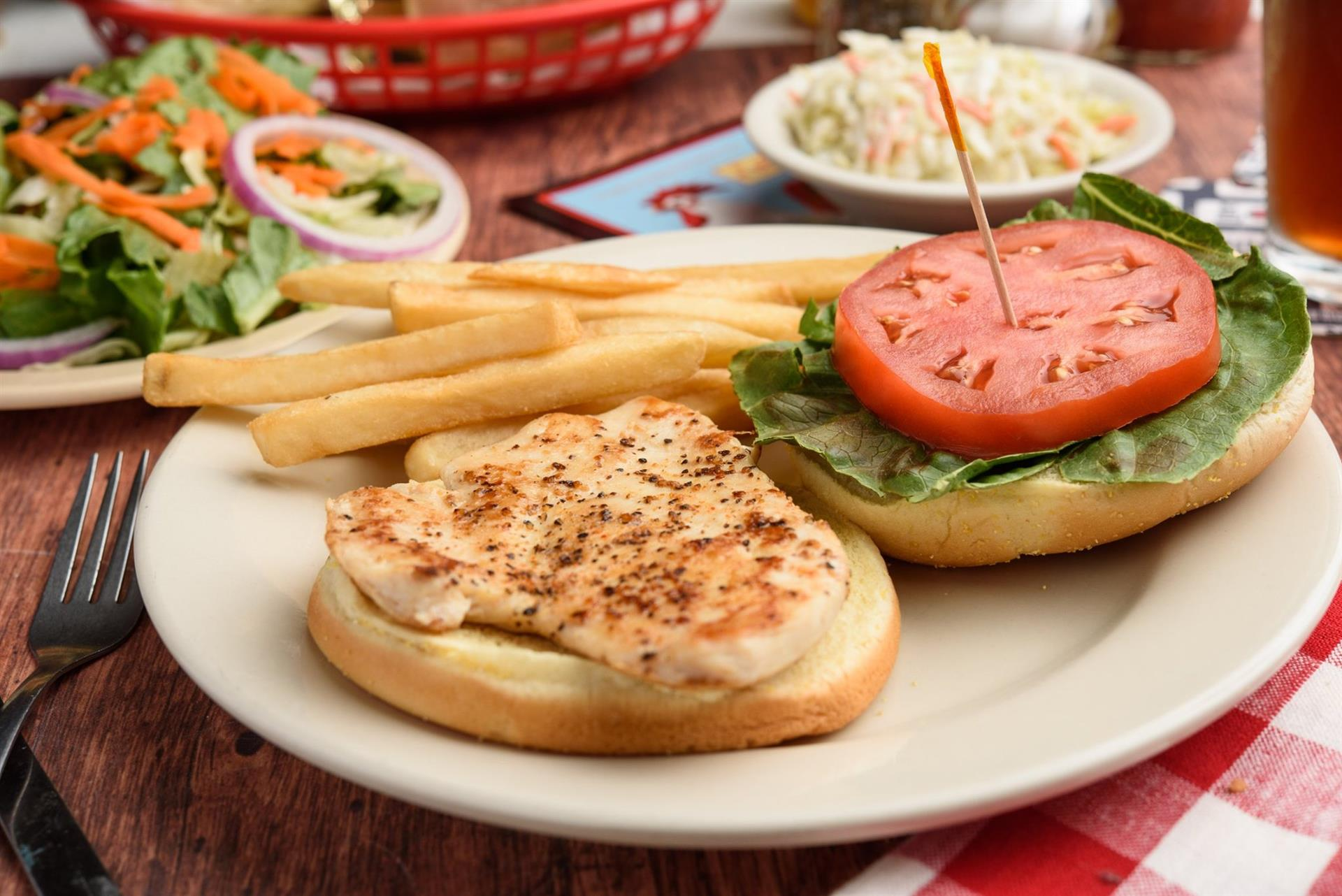 grilled chicken sandwich with tomato, lettuce, and a side of fries