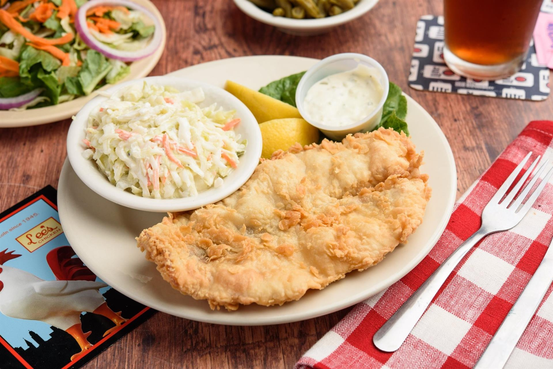 fried fish with a side of coleslaw and lemons